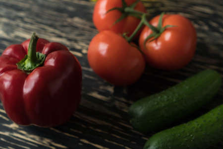 Fresh vegetables, cucumbers tomatoes peppers on wooden background. Imagens
