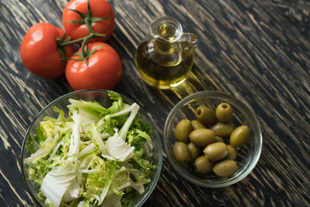 Salad leaves with olives, tomato and oil.