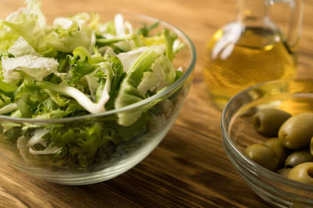 Salad leaves with olives and oil.
