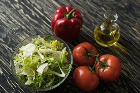 Healthy veggie salad ingridients. Tomato, lettuce, paprika and olive oil.
