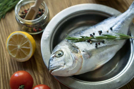 Raw fish cooking and ingredients. Dorado, lemon, herbs and spices.