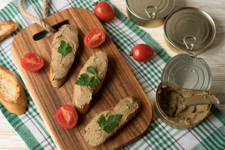 Liver pate on the bread on wooden tray.