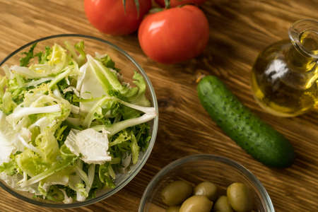 Salad ingridients. Tomato, lettuce, cucumber and olive oil.