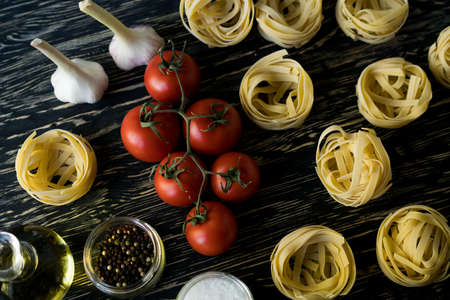 Pasta ingridients and spice on wooden surface. Stock Photo