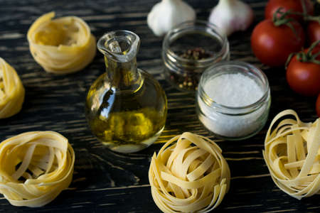 Pasta ingridients and spice on wooden surface. Standard-Bild