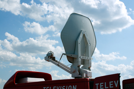 Television vehicle with parabolic antenna on the roof Фото со стока