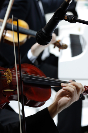 violins: A microphone in front of men playing on violins and piano  Microphone is in sharp focus, everything else is blur
