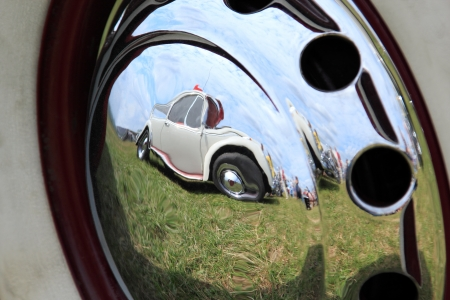 hubcap: Vintage car reflected in a chrome hubcap