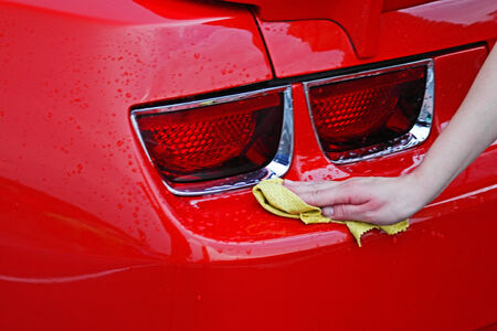 Washing a red car with a wet cloth  Stock Photo