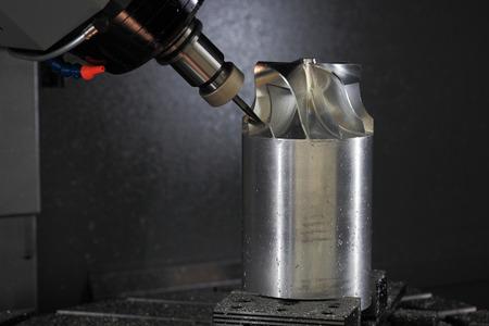 Five axis CNC machining center manufacturing jet engine turbine wheel.