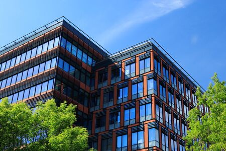 green office: Modern office building surrounded by trees with green foliage at summer day. Stock Photo