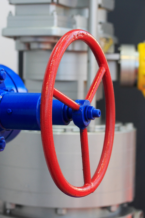 and gate: Red handwheel of the industrial steel gate valve. Stock Photo