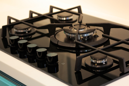 cooktop: Natural gas range cooker with black cooktop.