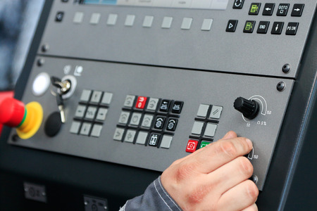 programmable: Worker operating the controls of CNC machine center.