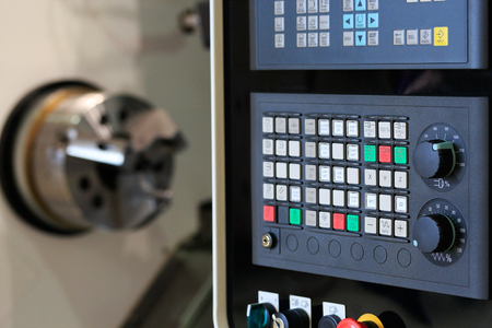 milling center: Close up of horizontal cnc turn mill machine with open door. Selective focus on control panel. Stock Photo