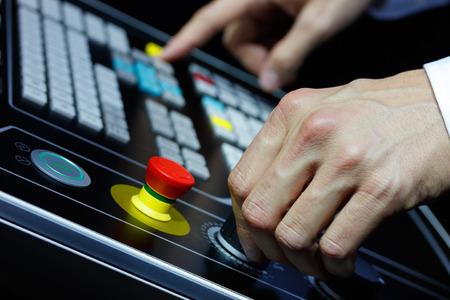 machining center: Operator controls the modern cnc machining center. Selective focus on hand.