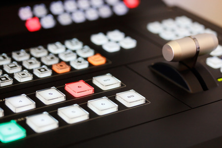 newsroom: Close up of video mixer control panel at tv broadcasting studio. Selective focus.