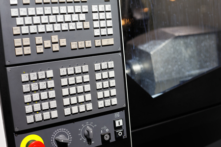 CNC machining center with control panel on the foreground. Selective focus.