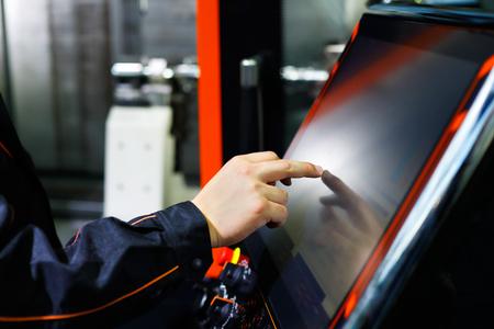 운전자는 터치 스크린을 사용하여 최신 CNC 선반 기계를 조정합니다. 선택적 포커스입니다.