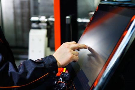 The operator adjusts modern CNC lathe machine using the touch screen. Selective focus. Reklamní fotografie