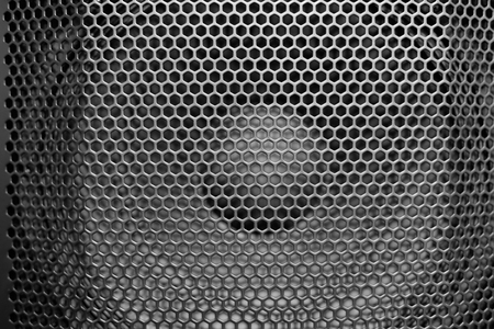 Black perforated metal speaker grill cover. Close up shot in black and white.
