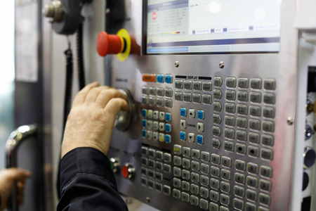 Operator working with controls of the CNC machine. Selective focus. Standard-Bild