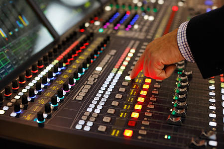 A sound engineer at the controls of an audio production console. Selective focus.