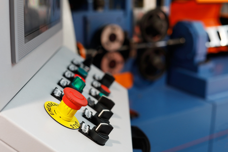 Control panel of the computer-aided manufacturing line. Selective focus on the emergency stop button.