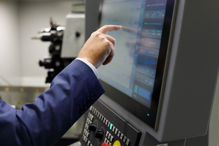 A service engineer using the touch screen to prepare cnc metalworking center for a new task. Selective focus. Standard-Bild