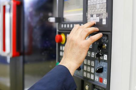 Operator working with CNC machining center using control panel. Selective focus. Standard-Bild