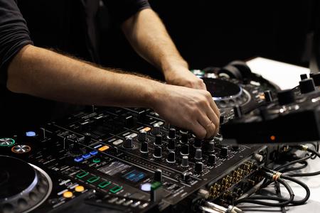 Dj hands mixing tracks on sound mixer controller.