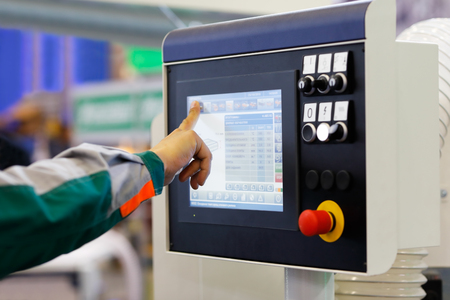 Operator using touchscreen prepares industrial equipment with CNC for a new task. Selective focus. Reklamní fotografie