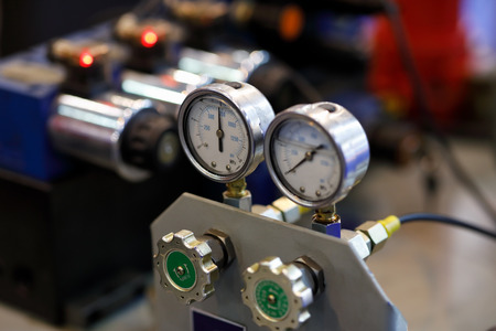 Hydraulic equipment with pressure gauges on an industrial machine. Selective focus.