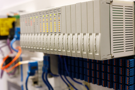 Programmable logic controller PLC modules installed in a rack. Selective focus.