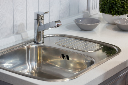 Sink with a tap in a kitchen. Selective focus. Standard-Bild - 118984528