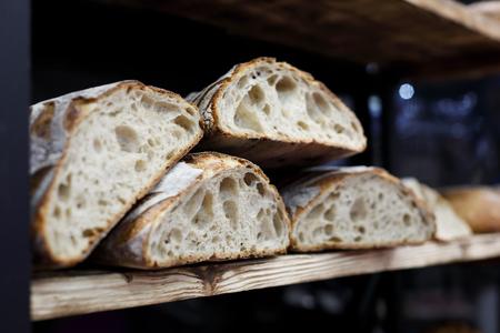 Artisan sourdough bread on the wooden shelf in the bakery. Selective focus.