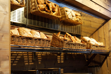 Baskets with different types of bread on the shelf in the bakery shop.