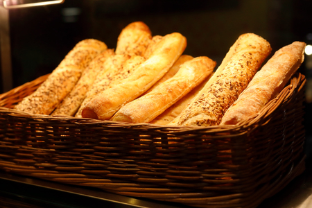 Basket with bread sticks on bakery counter. Selective focus.