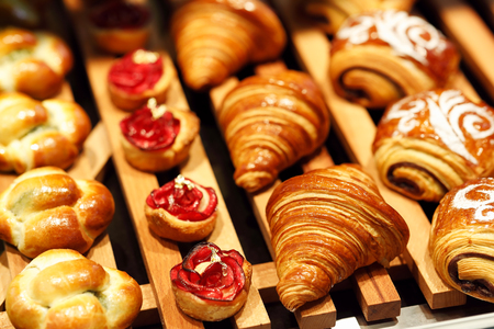 Freshly baked pastry on display in bakery shop. Selective focus.
