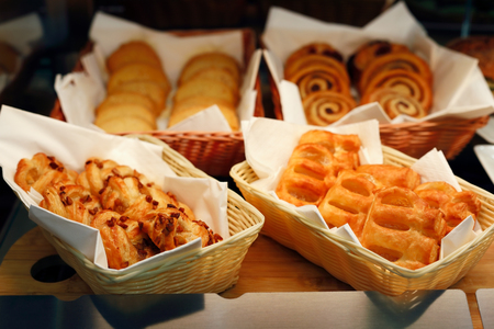 Pastry bakery display with assorted buns and jam puffs.