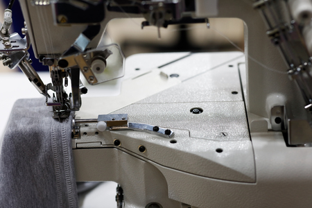 Industrial serger or overlocker sewing machine. Selective focus.