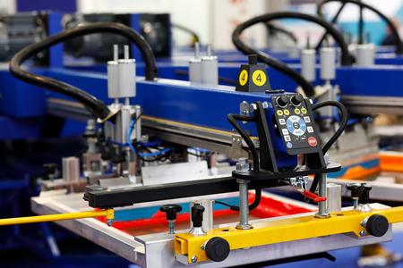 Automatic t-shirt screen printing rotary machine. Selective focus. Фото со стока