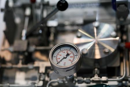 Industrial equipment with analog pressure gauge. Selective focus.