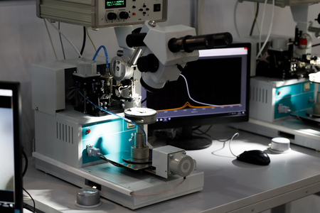 Manual ultrasonic wire bonding machines at semiconductor factory. Selective focus. Фото со стока
