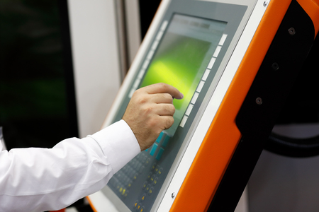 Engineer working with touch screen on the control panel of CNC laser cutting machine. Selective focus.
