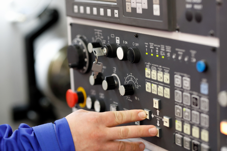 Engineer setup operation parameters of CNC lathe machine using buttons on the control panel. Selective focus.