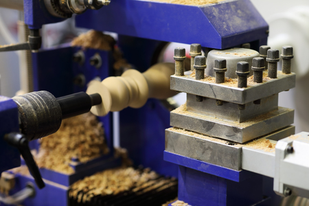 Wood carving process using woodturning lathe. Selective focus.