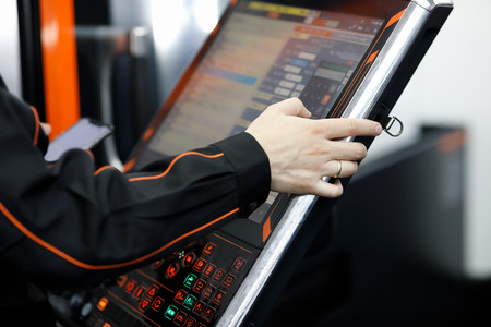 Operator of CNC machining center working with touch screen control panel.