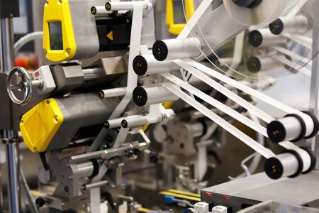 Closeup view of industrial automatic self adhesive labeling machine. Selective focus. Фото со стока