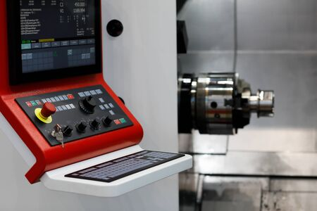 Modern CNC lathe machine with a control panel in the foreground. Selective focus.